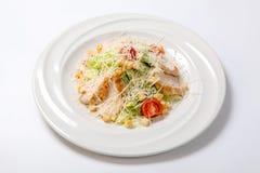 Insalata di Caesar con il pollo su un piatto rotondo bianco Immagine Stock