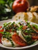 Insalata di Caprese con i pomodori, basilico e formaggio della mozzarella, con pane e prodotti nel fondo Fotografia Stock