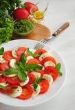 Insalata di Caprese con i pomodori, il formaggio di mozarella ed il basilico Immagini Stock