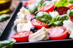 Insalata di Caprese Insalata Mediterranea Basilico e olio d'oliva dei pomodori ciliegia della mozzarella sulla vecchia tavola di  Fotografie Stock Libere da Diritti
