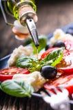 Insalata di Caprese Insalata Mediterranea Basilico e olio d'oliva dei pomodori ciliegia della mozzarella sulla vecchia tavola di  Fotografie Stock
