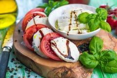 Insalata di Caprese Mozzarella, pomodori e foglie dell'erba del basilico immagini stock libere da diritti