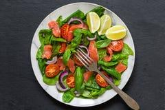 Insalata di color salmone con spinaci, i pomodori ciliegia, la cipolla rossa ed il basilico con la forcella in piatto di marmo bi fotografia stock