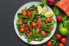 Insalata di color salmone con spinaci, i pomodori ciliegia, la cipolla rossa ed il basilico in piatto di marmo sopra fondo di pie fotografia stock