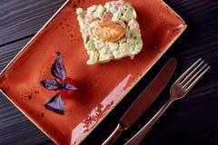 Insalata di Olivier con i gamberetti sul piatto rosso e sul fondo di legno nero fotografia stock