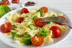 Insalata di pasta con i broccoli e la ciliegia del pomodoro con la forcella Alimento sano vegetariano fotografia stock