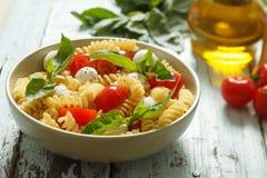 Insalata di pasta con i pomodori ciliegia e le foglie del basilico Immagini Stock Libere da Diritti