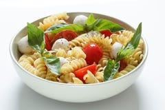 Insalata di pasta con i pomodori ciliegia e le foglie del basilico Immagine Stock Libera da Diritti