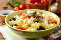 Insalata di pasta con i pomodori ciliegia, le olive nere, il feta ed il basilico su fondo di legno fotografia stock