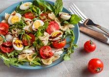 Insalata di pasta con le uova di quaglia, i pomodori, il rucola, la mozzarella ed il basilico fotografia stock libera da diritti