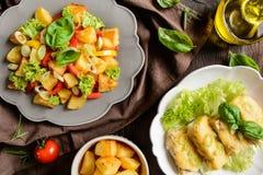 Insalata di patata fritta con lattuga, pepe, la cipolla ed il pesce al forno fi Fotografia Stock