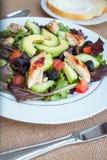 Insalata di pollo con l'avocado, i verdi misti, i cetrioli, i pomodori e le olive Fotografie Stock