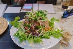 Insalata di tonno in piatto bianco sulla tavola immagini stock libere da diritti