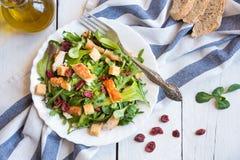 Insalata di verdura fresca con il pollo, arugola, crostini su legno bianco immagini stock