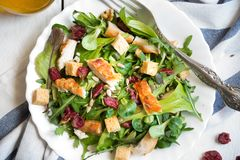 Insalata di verdura fresca con il pollo, arugola, crostini su legno bianco fotografia stock
