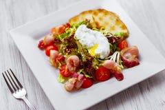 Insalata di verdure calda con bacon e l'uovo affogato immagini stock libere da diritti