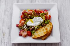 Insalata di verdure calda con bacon e l'uovo affogato fotografie stock libere da diritti