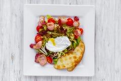 Insalata di verdure calda con bacon e l'uovo affogato fotografie stock