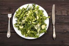 Insalata di verdure con gli ortaggi freschi e la rucola su una tavola di legno Insalata con gli ortaggi freschi verdi in una ciot Fotografia Stock Libera da Diritti