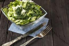 Insalata di verdure con gli ortaggi freschi su una tavola di legno Insalata con gli ortaggi freschi verdi in una ciotola di vetro Immagini Stock Libere da Diritti