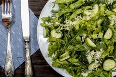 Insalata di verdure con gli ortaggi freschi su una tavola di legno Insalata con gli ortaggi freschi verdi in una ciotola di vetro Fotografie Stock