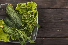 Insalata di verdure con gli ortaggi freschi su una tavola di legno Insalata con gli ortaggi freschi verdi in una ciotola di vetro Immagine Stock