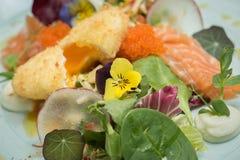 Insalata fredda con le uova di color salmone e rosse, le foglie verdi ed il flusso commestibile Fotografie Stock