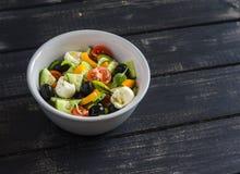 Insalata fresca con i pomodori, i cetrioli, i peperoni, le olive ed il formaggio in una ciotola ceramica Immagini Stock