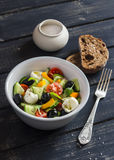 Insalata fresca con i pomodori, i cetrioli, i peperoni, le olive, il formaggio in una ciotola ceramica e la ciabatta del pane di  Immagini Stock