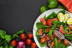 Insalata fresca con il salmone, gli spinaci, i pomodori ciliegia, la cipolla ed il basilico in piatto di marmo con la forcella su fotografie stock