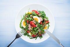 Insalata fresca con il tonno, i pomodori, le uova, la rucola e la senape sulla vista superiore del fondo di legno blu Immagini Stock