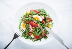 Insalata fresca con il tonno, i pomodori, le uova, la rucola e la senape sulla vista superiore del fondo strutturato bianco Fotografia Stock