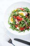 Insalata fresca con il tonno, i pomodori, le uova, la rucola e la senape sulla vista superiore del fondo strutturato bianco Fotografia Stock Libera da Diritti