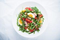 Insalata fresca con il tonno, i pomodori, le uova, la rucola e la senape sulla vista superiore del fondo strutturato bianco Immagine Stock Libera da Diritti