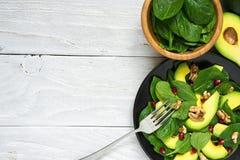 Insalata fresca con l'avocado, gli spinaci, il melograno e le noci in banda nera con la forcella Alimento sano immagini stock libere da diritti