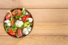Insalata fresca del cavolfiore con i pomodori, i broccoli, le olive, il peperone dolce, le erbe e le verdure in una ciotola su un Immagine Stock Libera da Diritti