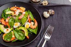 Insalata fresca e sana con i gamberetti, spinaci ed avocado su un blac Fotografie Stock Libere da Diritti