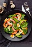Insalata fresca e sana con i gamberetti, spinaci ed avocado su un blac Fotografie Stock