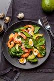 Insalata fresca e sana con i gamberetti, spinaci ed avocado su un blac Immagini Stock