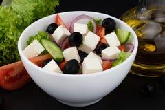 Insalata greca con gli ortaggi freschi, il feta e le olive nere su un fondo scuro fotografie stock