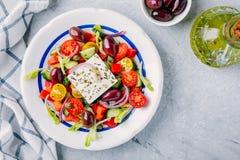 Insalata greca deliziosa con feta, olive, i pomodori, i cetrioli, la paprica e le cipolle rosse Fotografia Stock