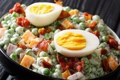 Insalata inglese di Pasqua con i piselli, gli uova sode, il bacon ed il cheddar freschi con il primo piano della salsa in una cio immagini stock libere da diritti