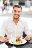 Insalata mangiatrice di uomini felice per la cena al ristorante Immagini Stock