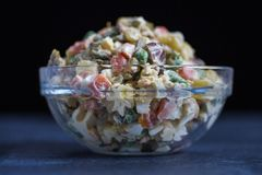 Insalata russa o insalata Olivier nel fondo scuro della ciotola di vetro fotografie stock