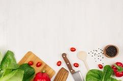 Insalata, spinaci, aneto, covoni del prezzemolo sulla plancia di legno bianca, vista superiore, confine decorativo immagini stock
