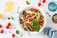Insalata spiralized ketogenic dello zucchino del vegano con i semi di zucca del pomodoro dell'avocado fotografia stock libera da diritti