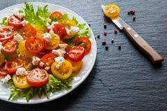 Insalata variopinta, foglie verdi fresche e pomodori ciliegia rossi e gialli affettati, piatto bianco, coltello, fondo di pietra  Immagini Stock