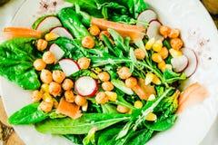 Insalata verde con la rucola, il mais, le carote ed i ceci al forno guar immagini stock