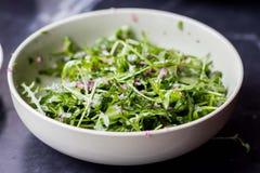Insalata verde fresca con la rucola, salsa della cipolla, olio d'oliva Immagine Stock