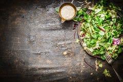 Insalata verde mista fresca con olio che veste fondo di legno rustico, vista superiore Alimento sano Fotografia Stock